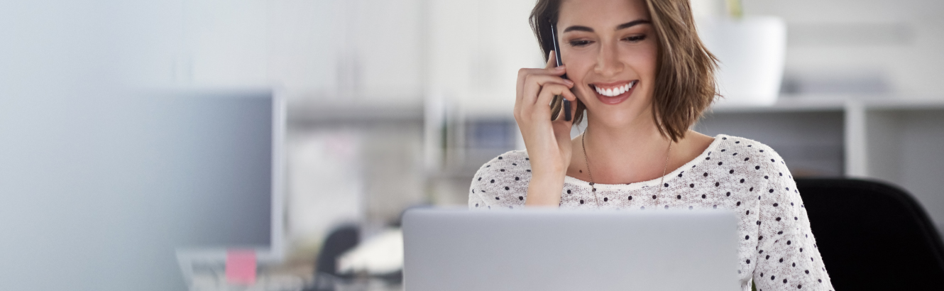A happy, young woman at work on the phone while browsing her laptop